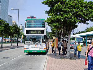 People wait under the trees outside the central ferry pier as they wait for bus 15 to The Peak